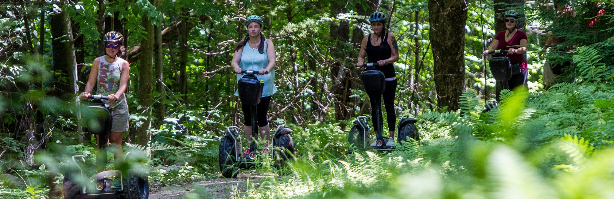 Ladies driving Segways through the woods
