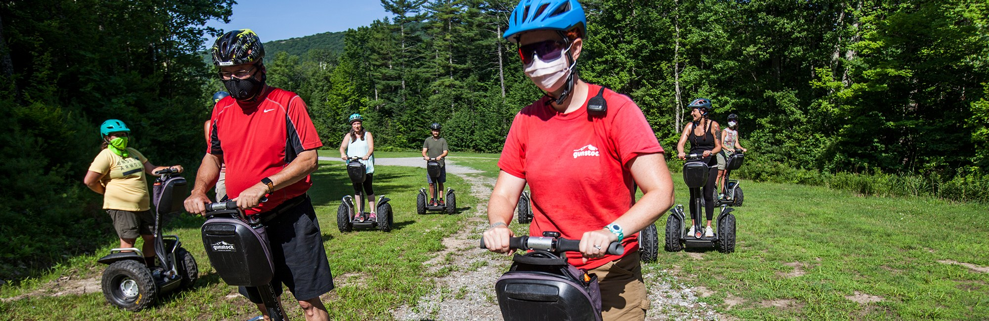 People driving Segways while wearing masks